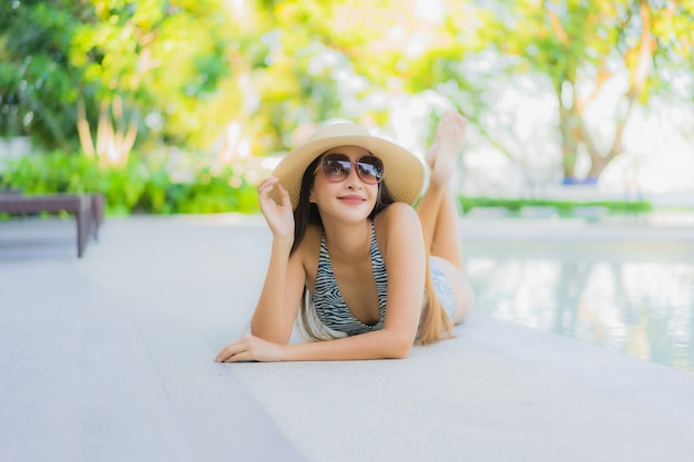 Sonrisa feliz de hermosas mujeres asiáticas jóvenes relajarse alrededor de la piscina al aire libre en el hotel resort