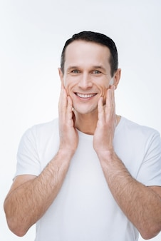 Sonrisa feliz. hombre agradable feliz positivo de pie contra el fondo blanco y sonriendo mientras toca sus mejillas
