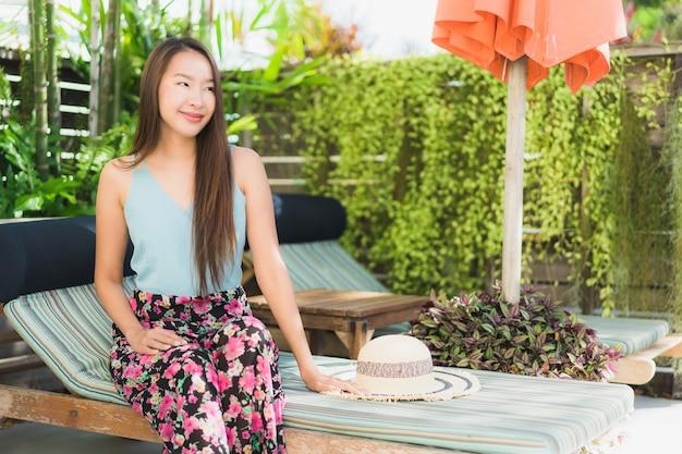 La sonrisa feliz de la mujer asiática joven hermosa y se relaja en piscina