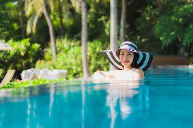 Sonrisa feliz de la mujer asiática joven hermosa del retrato en piscina alrededor del centro turístico y del hotel