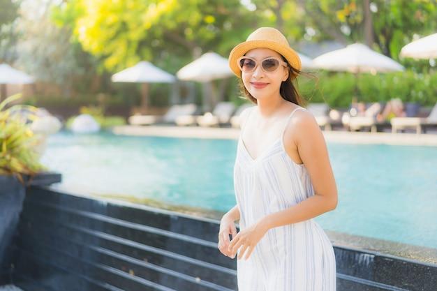 La sonrisa feliz de la mujer asiática joven hermosa del retrato y se relaja alrededor de piscina en centro turístico del hotel