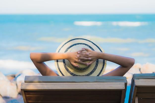La sonrisa feliz de la mujer asiática joven hermosa del retrato se relaja alrededor de la playa y del mar neary