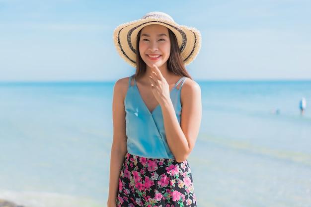 La sonrisa feliz de la mujer asiática joven hermosa del retrato se relaja alrededor de la playa océano y mar