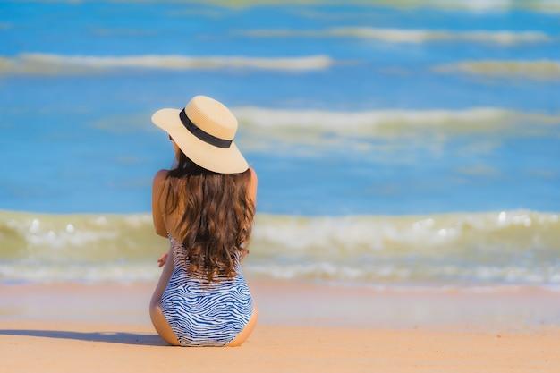 La sonrisa feliz de la mujer asiática joven hermosa del retrato se relaja en el océano tropical del mar de la playa para el viaje del ocio