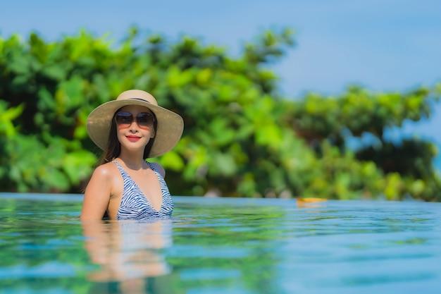 La sonrisa feliz de la mujer asiática joven hermosa del retrato se relaja en piscina en la playa neary del océano del mar del centro turístico del hotel en el cielo azul