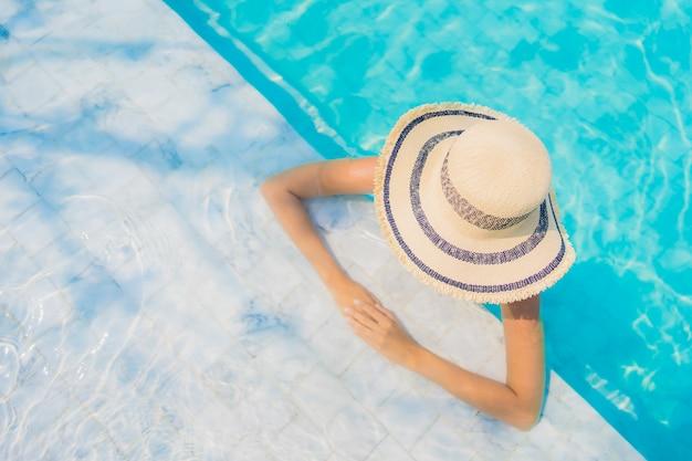 La sonrisa feliz de la mujer asiática joven hermosa del retrato se relaja en la piscina para las vacaciones del viaje