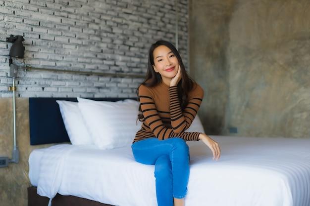 La sonrisa feliz de la mujer asiática joven se relaja en cama en dormitorio