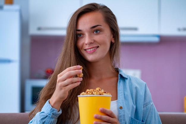 Sonrisa feliz mujer atractiva descansando y comiendo crujientes palomitas de caramelo durante ver películas de comedia en casa. película de palomitas de maíz