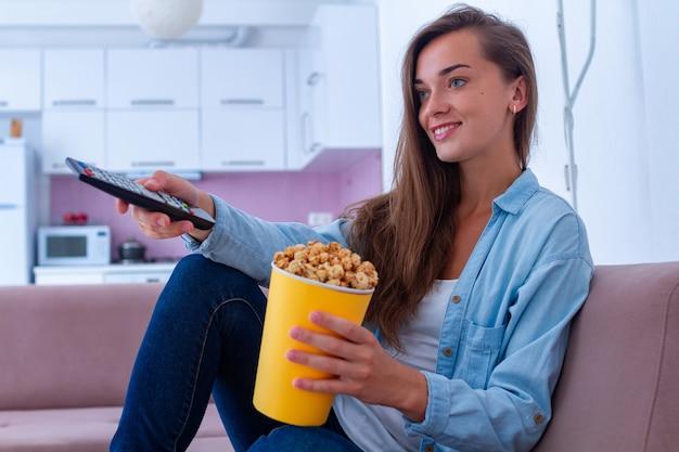Sonrisa feliz mujer descansando y comiendo crujientes palomitas de caramelo durante la televisión en casa