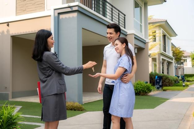 Sonrisa feliz pareja joven tomar llaves nueva casa grande del agente inmobiliario