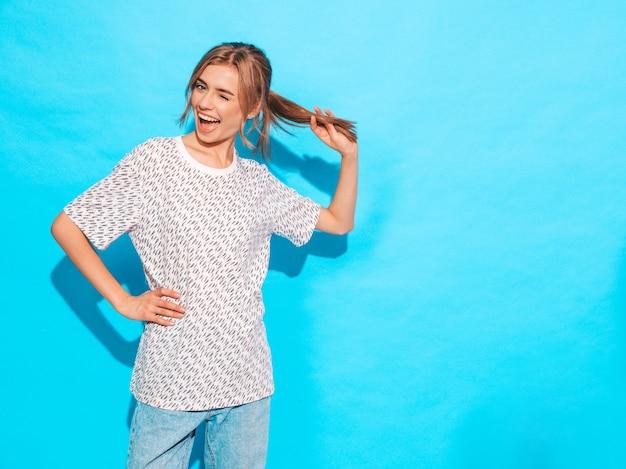 Sonrisa femenina positiva modelo divertido que presenta cerca de la pared azul en estudio jugando con el pelo y los guiños