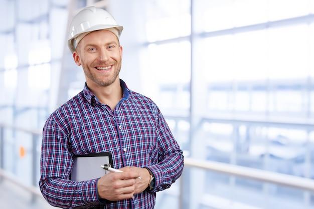 Sonrisa joven feliz del arquitecto del hombre de negocios