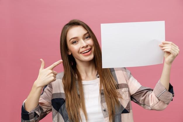 Sonrisa joven de la mujer que se coloca que señala su dedo en una tarjeta en blanco.