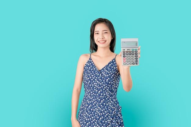 Sonrisa mujer asiática que sostiene la calculadora aislada en fondo azul.