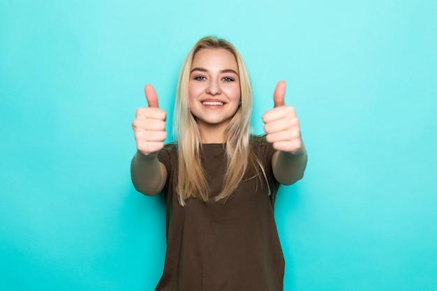 Sonrisa mujer bastante joven que muestra los pulgares para arriba aislados en la pared azul