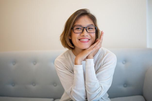 Sonrisa mujer bastante joven que se sienta en el sofá y que presenta en la cámara
