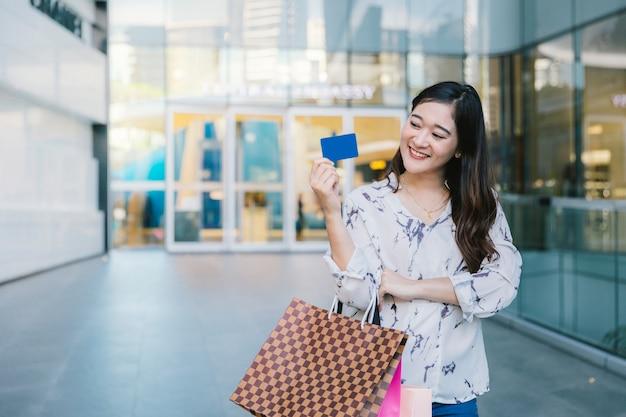 Sonrisa de mujer con bolsas de compras disfrutar de uso de tarjeta de crédito en centro comercial
