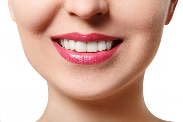 La sonrisa de una mujer joven con dientes blancos perfectos. primer plano aislado en blanco