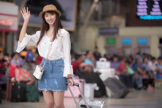 Sonrisa de mujer turista asiática saludando con la mano en la estación de tren