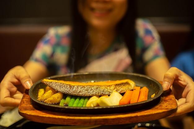Sonrisa a mujeres sosteniendo filete de salmón en placa negra