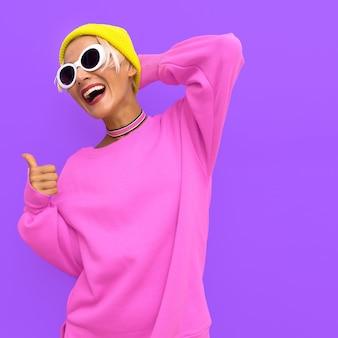 Sonrisa de niña en accesorios de moda beanie cap gafas de sol y gargantilla vibraciones urbanas de moda coloridas