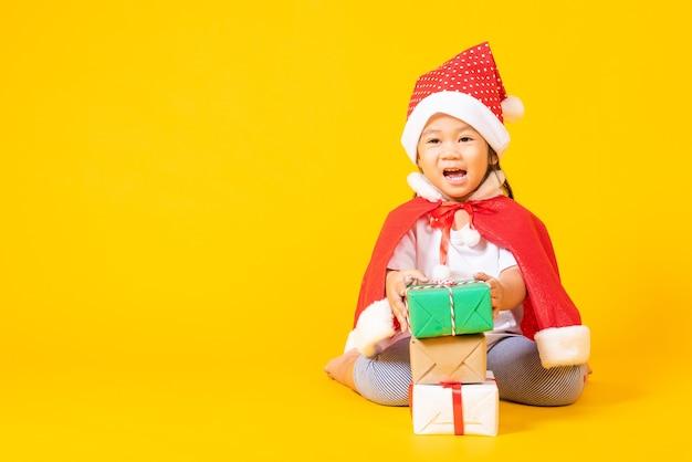 Sonrisa de niña asiática vestida de rojo santa el concepto de día de navidad