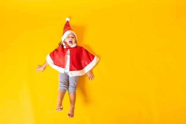Sonrisa de niña vestida de rojo santa el concepto de vacaciones el día de navidad