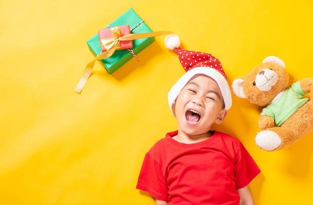 Sonrisa de niño asiático vestido de rojo santa el concepto de vacaciones navidad día de navidad