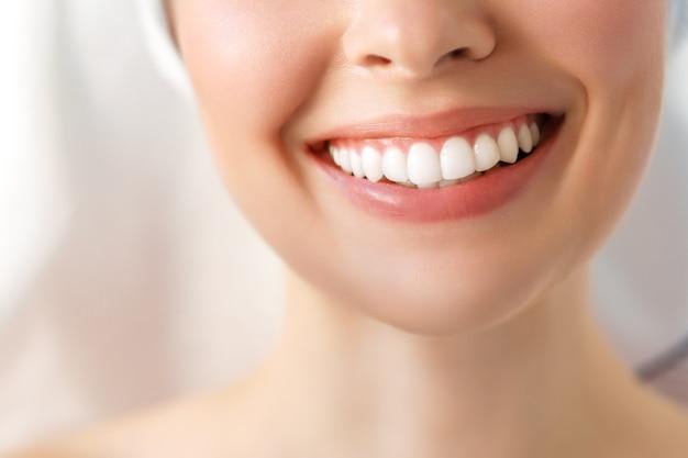 Sonrisa perfecta de dientes sanos de una mujer joven. blanqueamiento dental. la imagen simboliza la odontología del cuidado bucal,