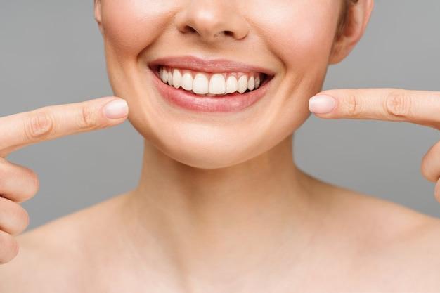 La sonrisa perfecta de los dientes sanos de una mujer joven que blanquea los dientes simboliza la imagen del paciente de la clínica dental