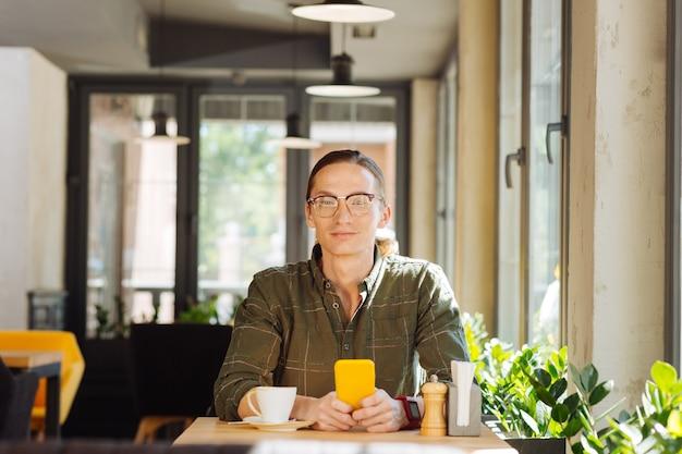 Sonrisa positiva. hombre atractivo guapo mirándote mientras está sentado en la mesa con su teléfono inteligente en sus manos