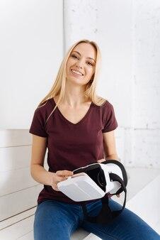 Sonrisa sincera. mujer atractiva que expresa positividad y sostiene un nuevo dispositivo mientras está sentada en muebles blancos