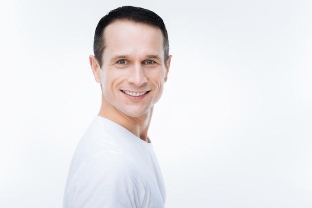 Sonrisa sincera. retrato de un hombre agradable feliz alegre sonriendo mientras está de pie contra el fondo blanco.