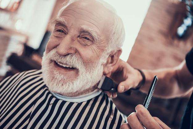 Sonrisas adultas de cabello gris durante el corte de pelo en la nuca.