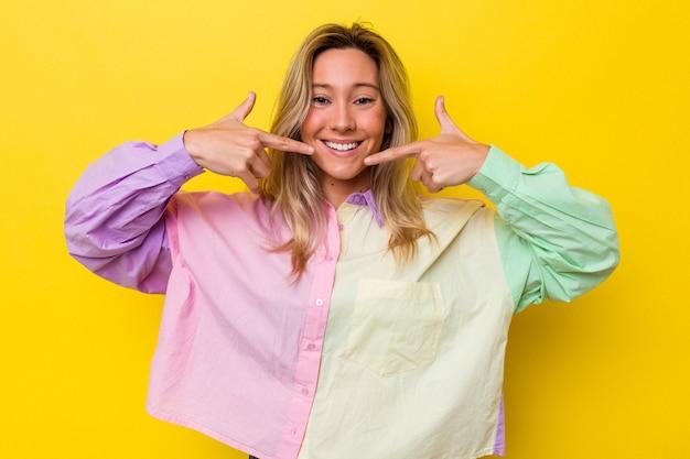 Sonrisas aisladas joven mujer australiana, señalando con el dedo a la boca.