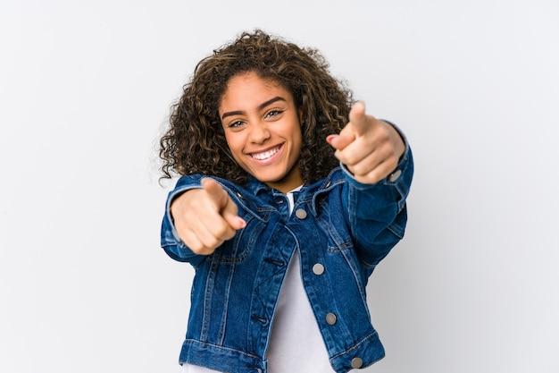 Sonrisas alegres de la mujer afroamericana joven que señalan al frente.