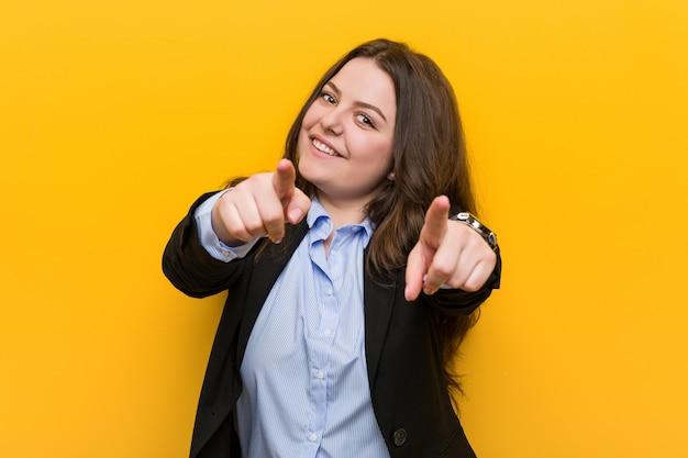 Sonrisas alegres de la mujer de negocios caucásica del tamaño extra grande joven que señalan al frente.