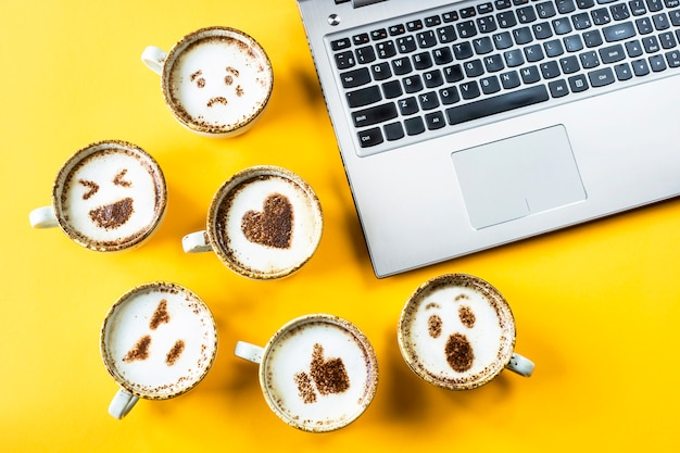 Sonrisas de emoji pintadas en tazas de capuchino junto al portátil.