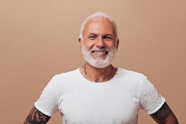 Sonrisas lindas hombre alegre en pared beige