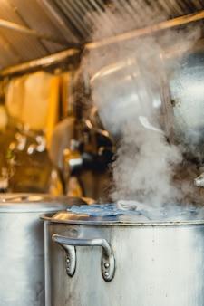 Sopa de agua hirviendo a fuego lento en una olla grande o caldera en la cocina del restaurante japonés