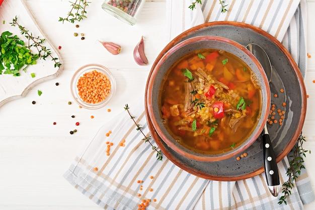 Sopa apetitosa con lentejas rojas, carne, pimentón rojo y tomillo fragante.