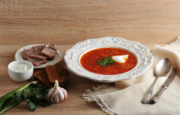 Sopa en un bol con eneldo, crema agria y pan negro sobre superficie de madera