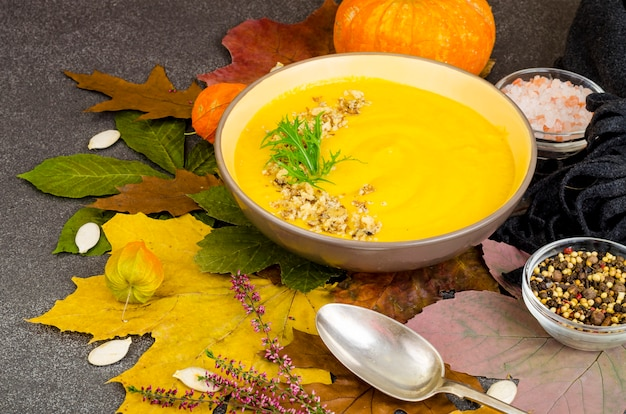 Sopa de calabaza caliente sobre fondo de hojas secas de otoño.