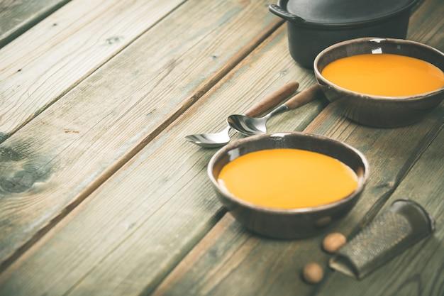 Sopa de calabaza en mesa de madera, acogedor concepto de comida