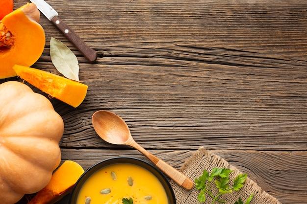 Sopa de calabaza plana en un tazón con calabaza y cuchara de madera con espacio de copia