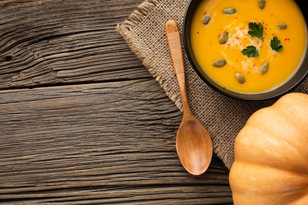 Sopa de calabaza plana en un tazón y cuchara de madera con espacio de copia