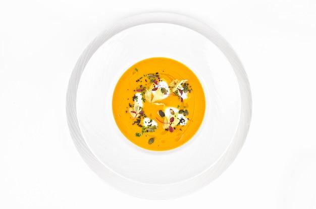 Sopa de calabaza con queso crema sobre un fondo blanco.