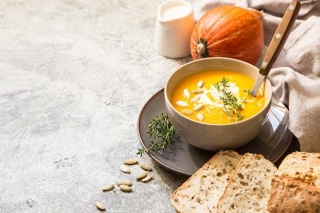 Sopa de calabaza con semillas de calabaza, pan crujiente y tomillo con copyspace
