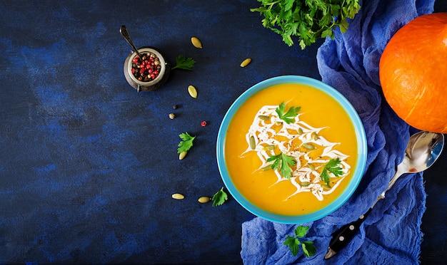 Sopa de calabaza en un tazón servido con perejil y semillas de calabaza.