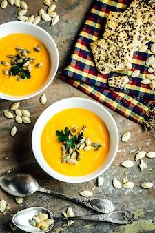 Sopa de calabaza y zanahoria con crema y perejil en mesa de madera